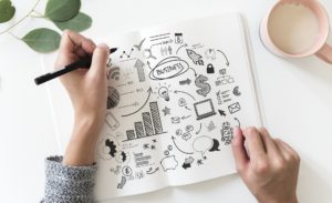 Hand doodling in a notebook sketches regarding saving money